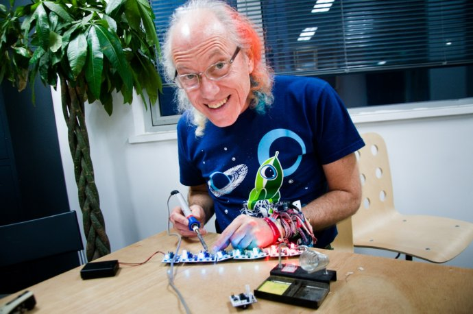 picture of mitch soldering with a space cartoon t-shirt and orange and blue hair